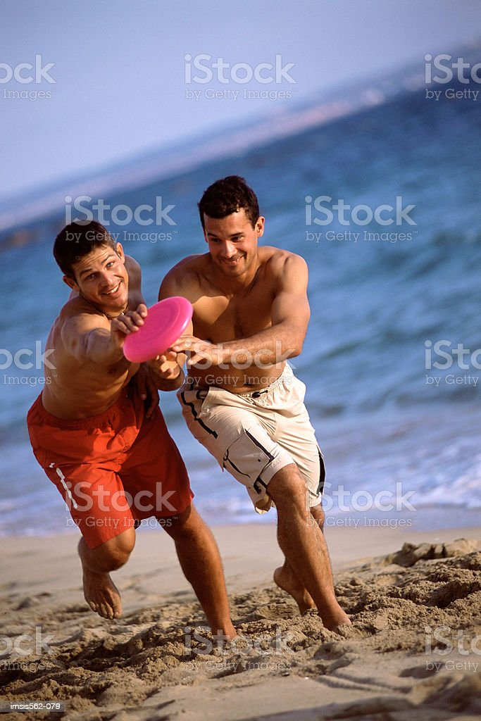 Males playing with a flying disc on beach royalty-free stock photo