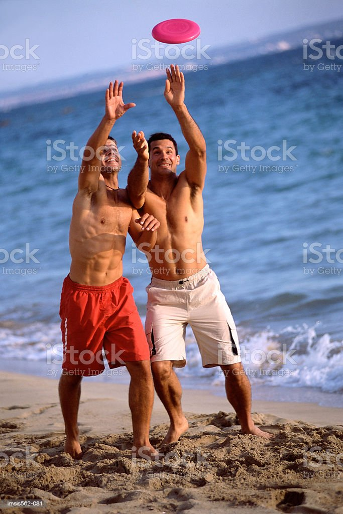 Males playing with a flying disc on beach 免版稅 stock photo