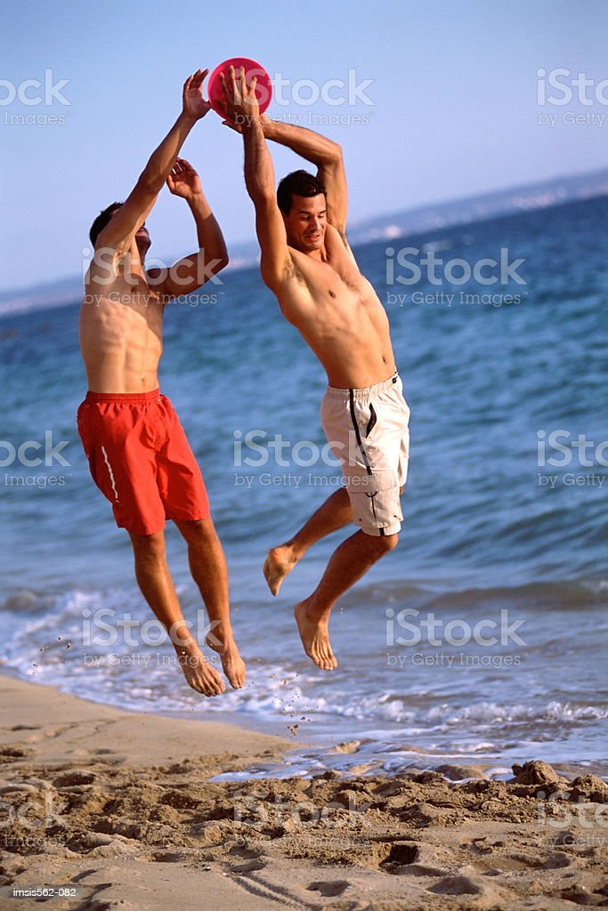 Males playing with a flying disc on beach royalty free stockfoto