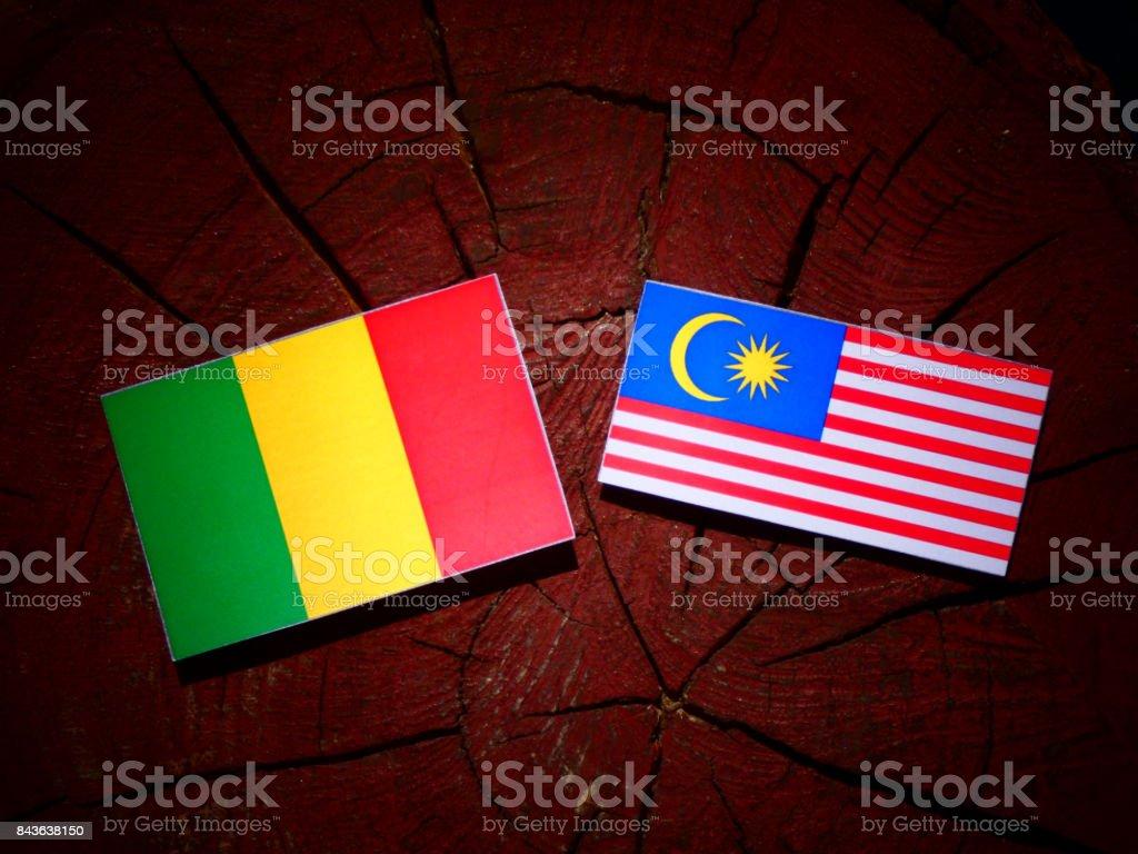 Bandeira do Mali com a bandeira da Malásia em um toco de árvore isolada - foto de acervo