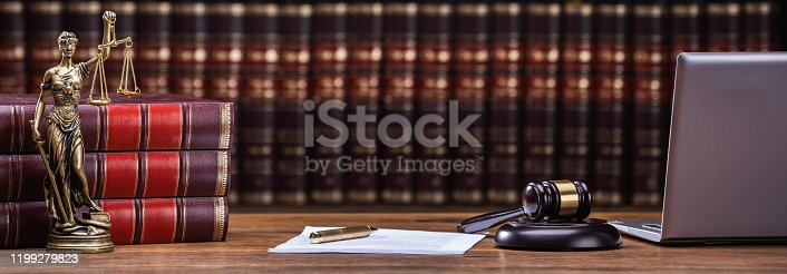 Closeup Of Mallet And Legal Book With Justice Scale On Table In Courtroom