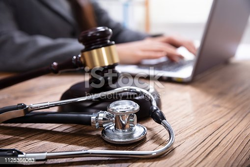 istock Mallet And Stethoscope On Gavel Over The Office Desk 1125366083