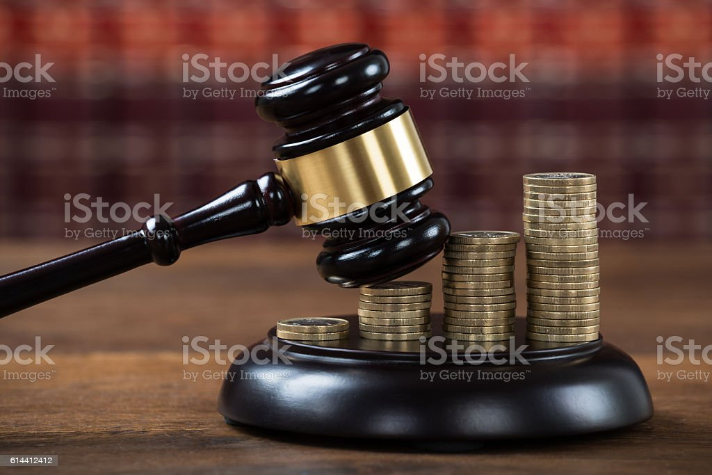 Mallet Being Hit On Stacked Coins In Courtroom stock photo