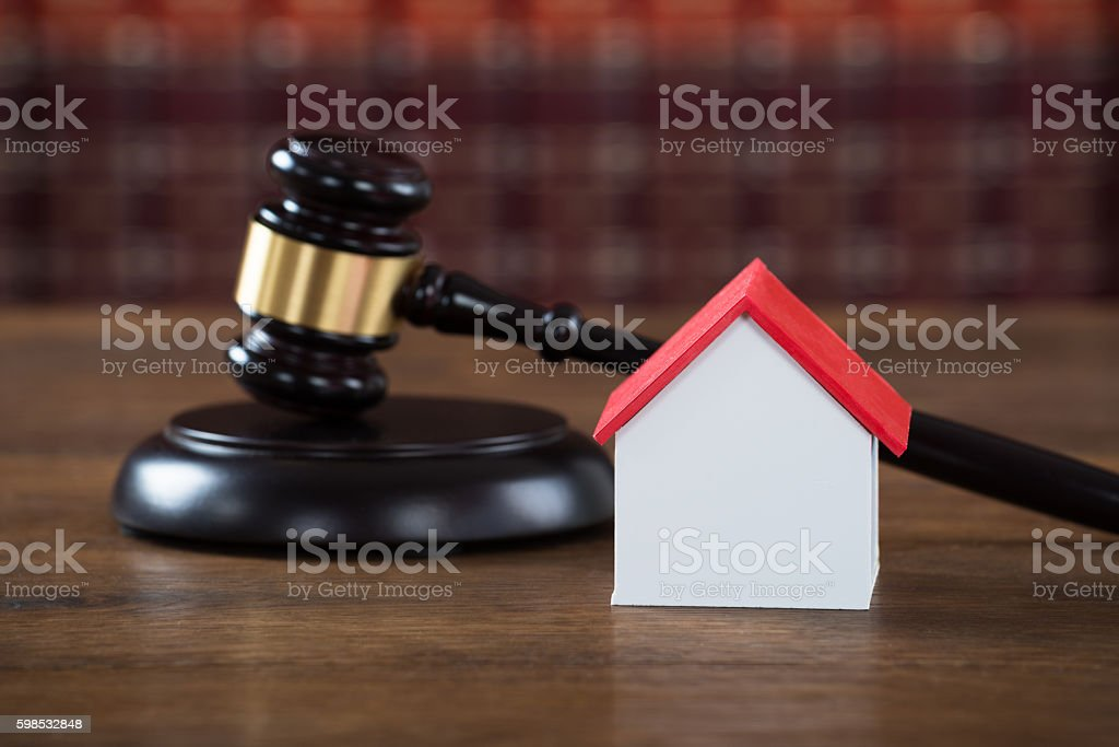 Mallet With House Model On Table In Courtroom stock photo