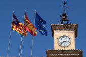 Palma, Mallorca, Spain - April 9, 2019: the flags of Mallorca (Aragon-Catalonia), Spain and the European Union (EU), flying by the clock tower and weather vane of the Consolat de Mar.  The Consulat de Mar was built around 1600 and is today used as the offices of the President of the Balearic Islands.