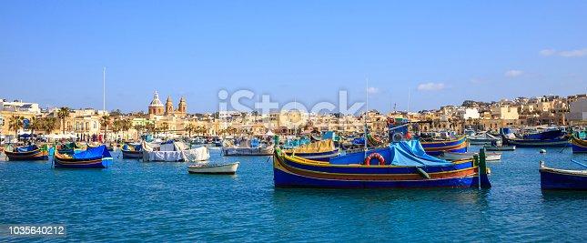istock Malta, Marsaxlokk historic port full of boats. Blue sky and village background. Close up view, banner. 1035640212