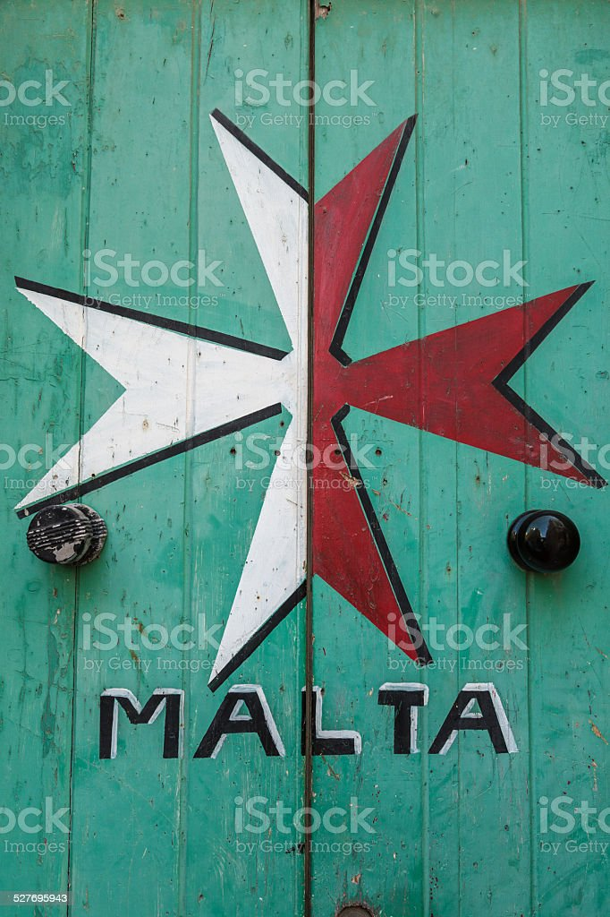 Maltese Cross painted onto an old, wooden, green door stock photo