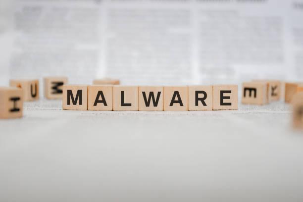 Malware Word Written In Wooden Cube - Newspaper stock photo