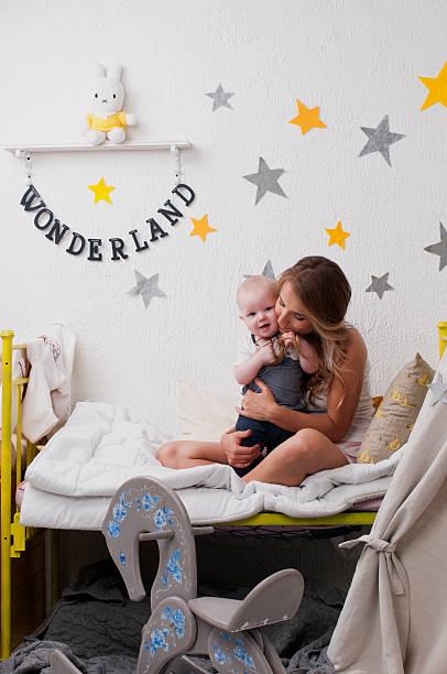 mam umarmen ihr baby in einem babybett am abend - tipi bett stock-fotos und bilder