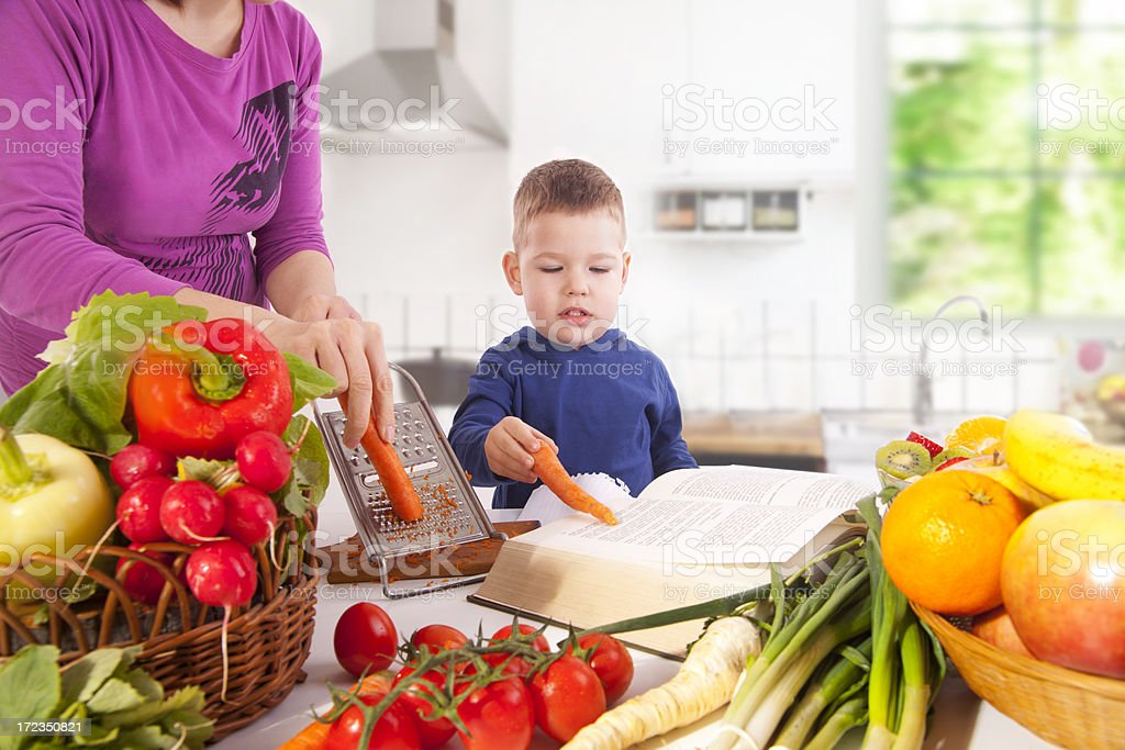 Mamma teaches her son how to cut vegetables royalty-free stock photo