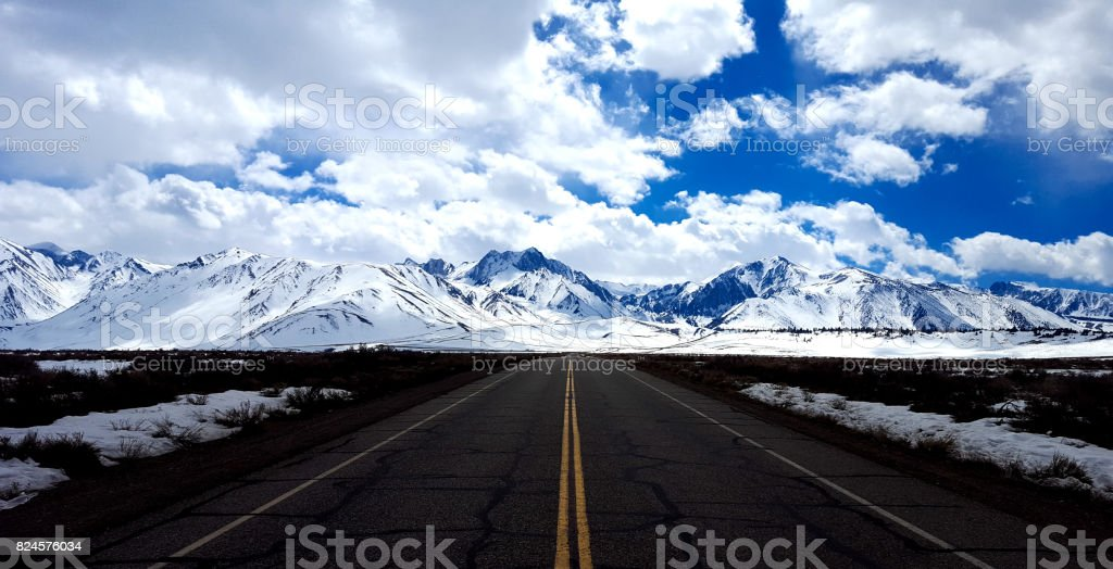 Mammoth, CA: Long Lonely Highway into Snowcapped Mountains stock photo