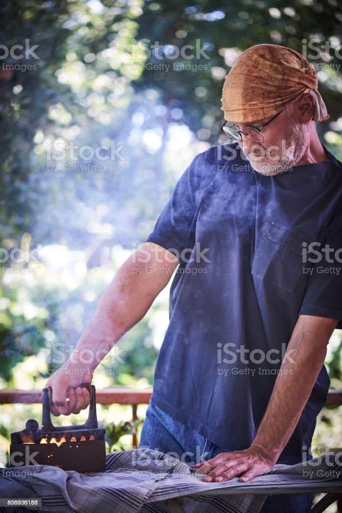 Man 50+ ironing clothes at home on sunlit terrace with a ancient iron stock photo