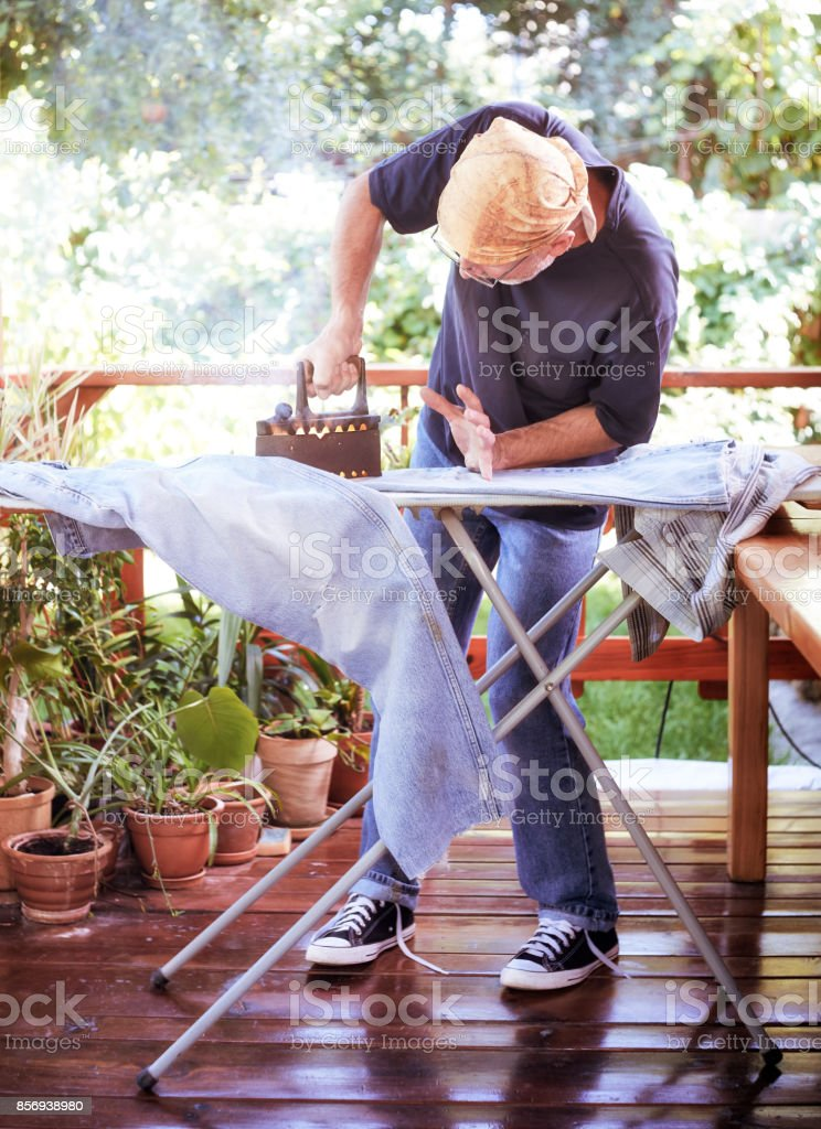 Man 50+ ironing jeans at home on sunlit terrace with a ancient iron stock photo