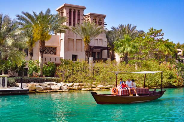 ein mann, eine frau und kinder fahren ein altes hölzernes boot entlang des kanals im madinat vorbei an den gebäuden der arabischen kultur - dubai urlaub stock-fotos und bilder