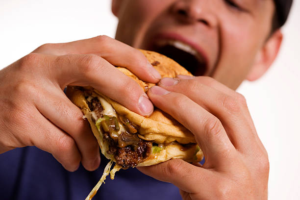 A man about to devour a big greasy burger stock photo