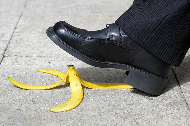 Man about to step on a banana peel on the sidewalk stock photo
