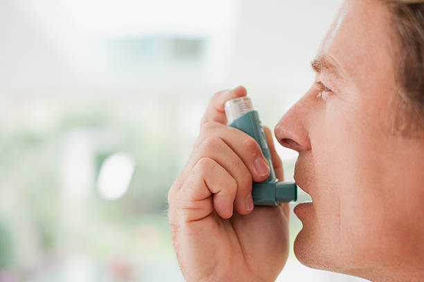 Man about to use asthma inhaler stock photo