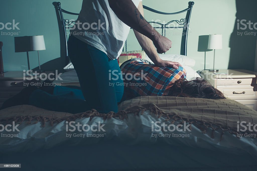 Man abusing his wife on a bed