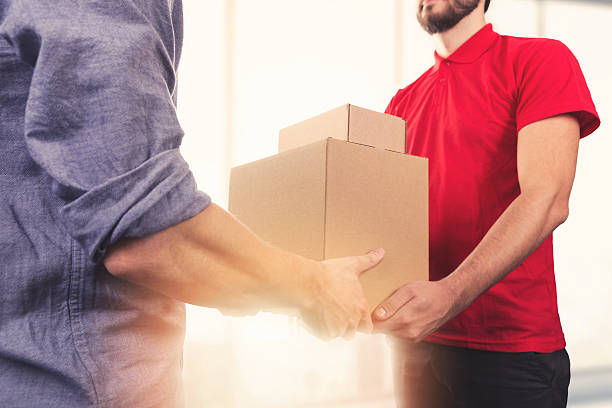 man accepting a delivery of boxes from delivery service courier stock photo