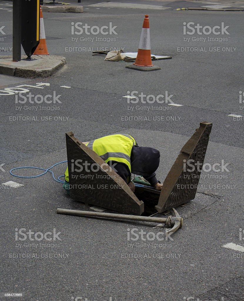 Man accessing a manhole royalty-free stock photo