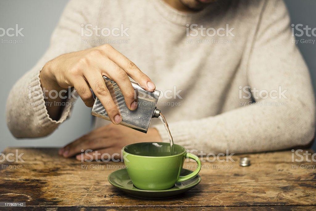 Man adding alcohol to his coffee stock photo