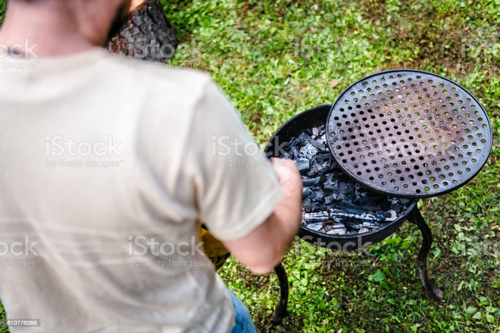 Man adding charcoal to the grill stock photo