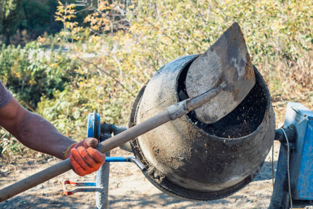 Man adding components to a cement mixer stock photo