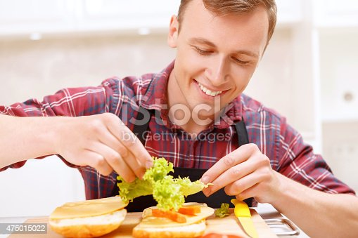 istock Man adding lettuce leaves  to his sandwich 475015022