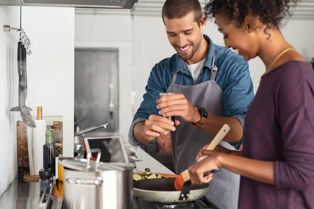 uomo che aggiunge pepe in salsa di pomodoro - cucinare foto e immagini stock