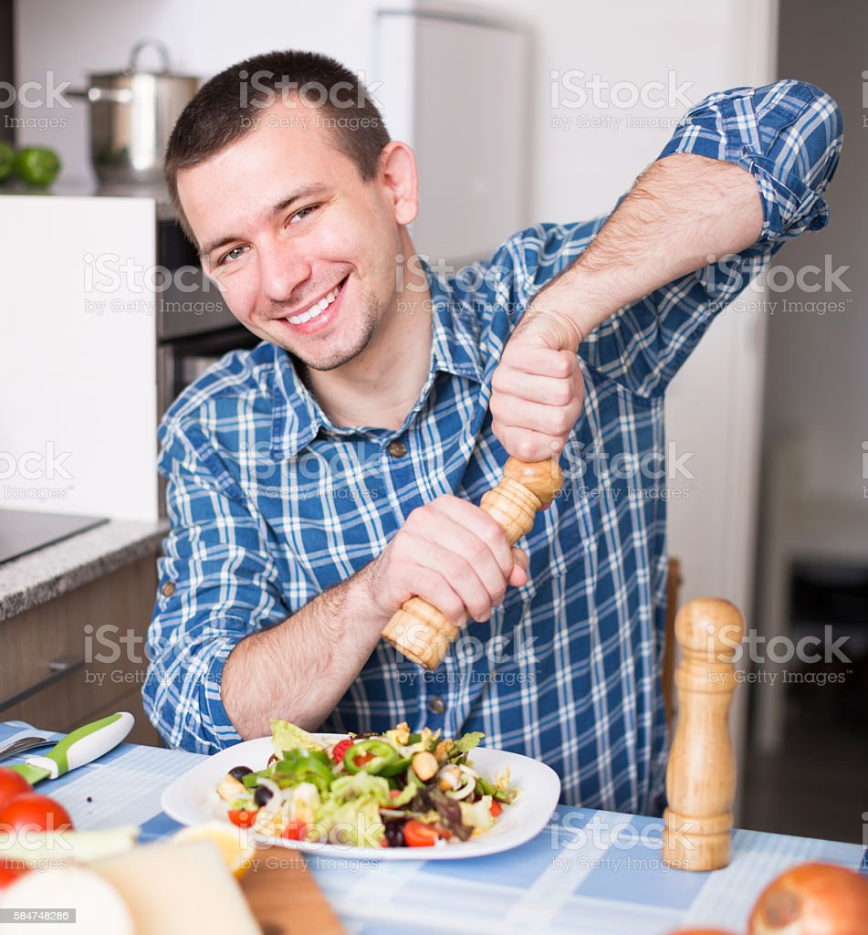 man adding spice to the salad – Foto