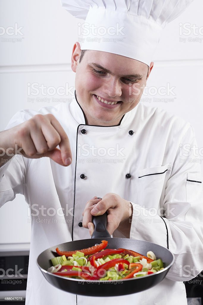 Man adding spices into vegetables royalty-free stock photo