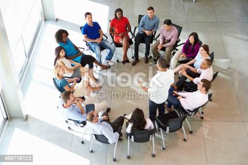 504879112istockphoto Man addressing muti-cultural office staff seated in circle 469718123