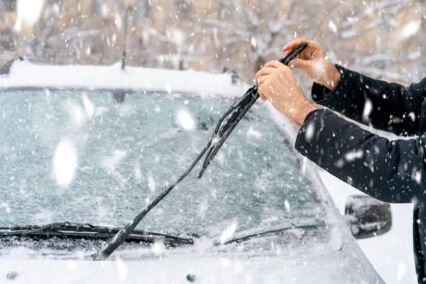 man aan te passen en het schoonmaken van de ruitenwissers van auto in besneeuwde weer b - voorruit stockfoto's en -beelden