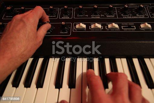 istock Man adjusting and playing vintafge analogue music synthesizer 641795898