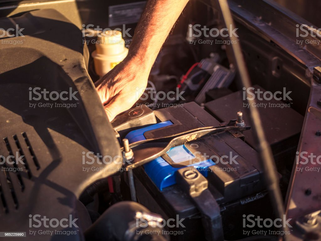 man adjusting car battery in the garage royalty-free stock photo
