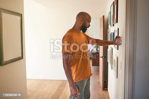 Man Adjusting Digital Central Heating Thermostat At Home