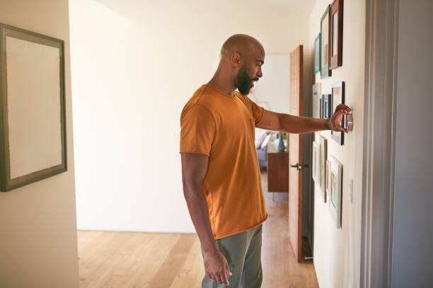 Man Adjusting Digital Central Heating Thermostat At Home stock photo