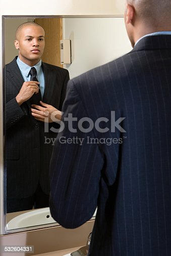 istock Man adjusting his tie in mirror 532604331