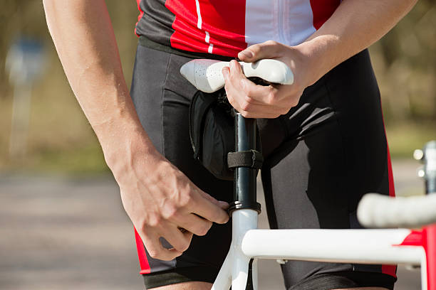 Man Adjusting Seat Of Bicycle stock photo