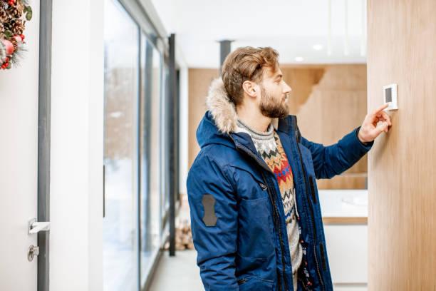 man temperatuur aanpassen met thermostaat thuis - bijstellen stockfoto's en -beelden