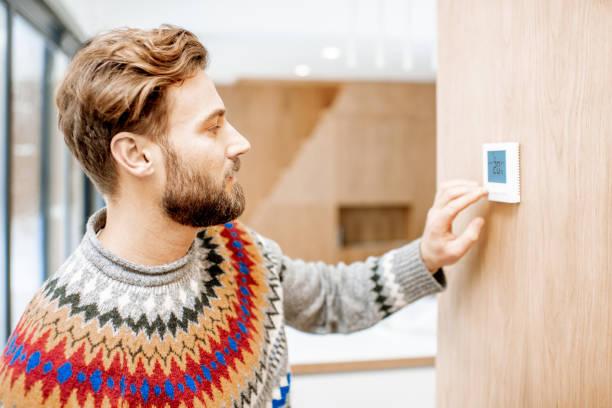 hombre ajuste de temperatura con termostato en casa - calor fotografías e imágenes de stock