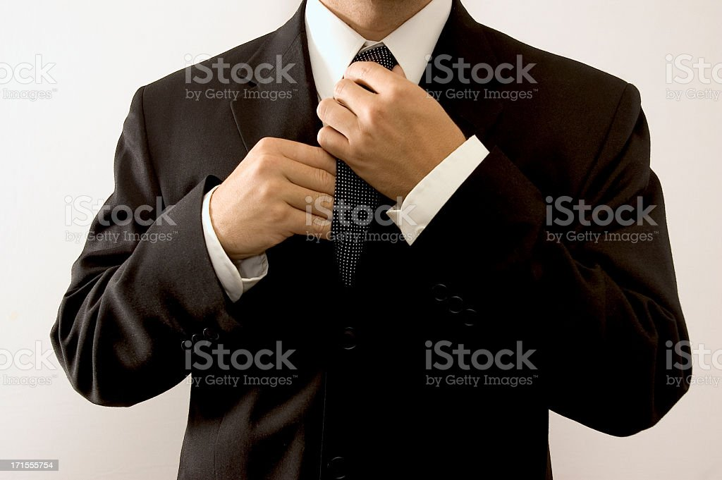 A man adjusting the tie of his suit royalty-free stock photo