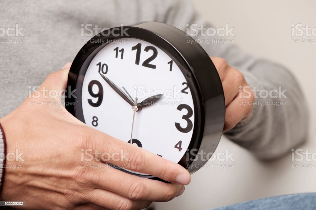 man adjusting the time of a clock stock photo