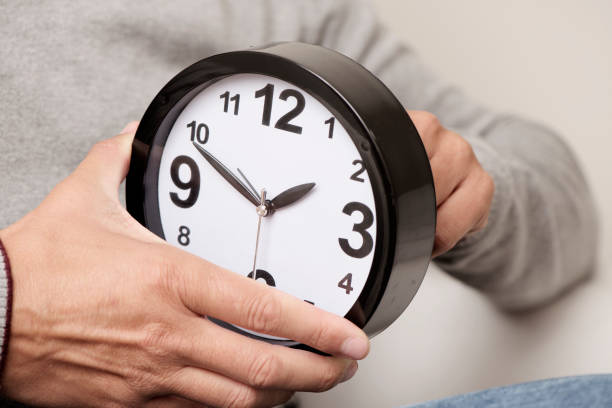 man adjusting the time of a clock closeup of a young caucasian man adjusting the time of a clock daylight savings stock pictures, royalty-free photos & images