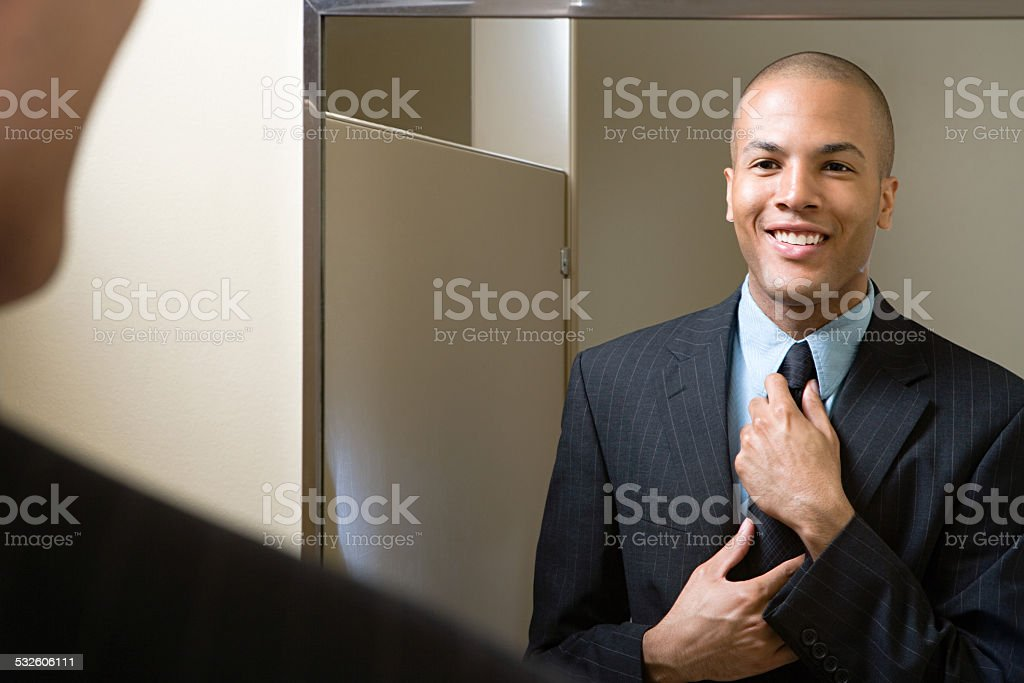 Man adjusting tie in mirror stock photo