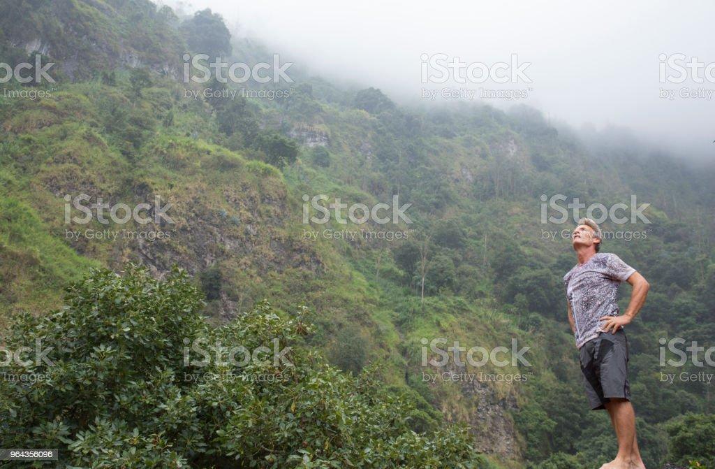 Homem admira floresta tropical sobre os flancos do vulcão - Foto de stock de 55-59 anos royalty-free
