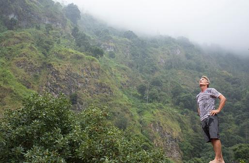 Foto de Homem Admira Floresta Tropical Sobre Os Flancos Do Vulcão e mais fotos de stock de 55-59 anos