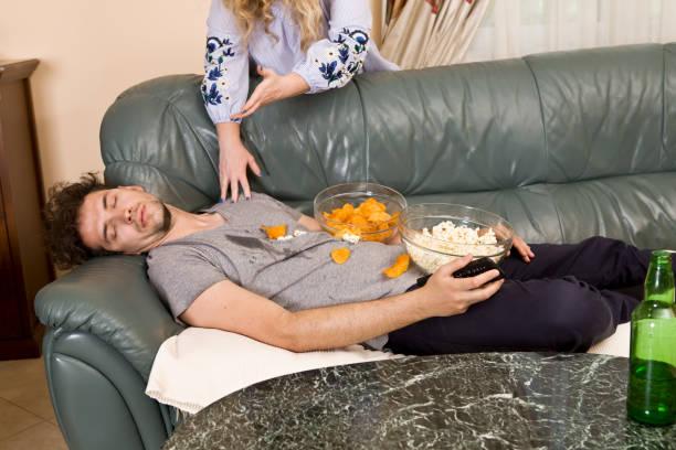homem após pesado festejando em casa. mulher zangada - junk food - fotografias e filmes do acervo