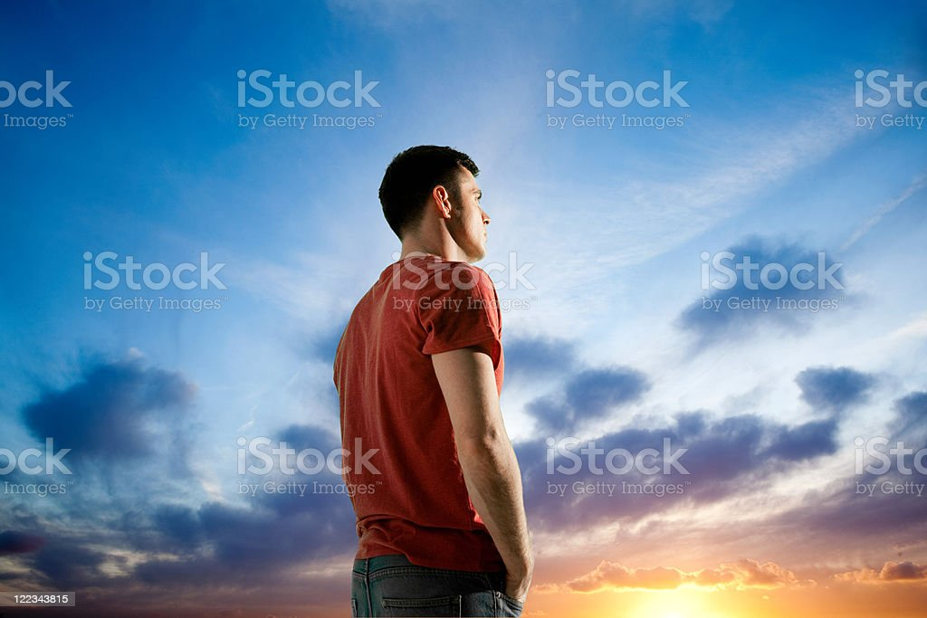 Man against dramatic sunset, looking away stock photo