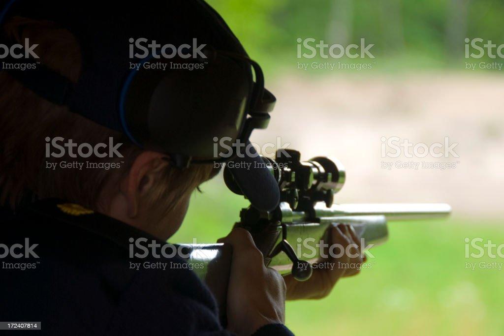 Man aiming a rifle at a target stock photo